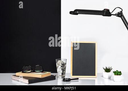 Holzrahmen mit schwarzen Platz für Text. Mock up. Stilvolle Inneneinrichtung. Grüne Pflanze in einem weißen Topf auf Schwarz-weiße Wand im Hintergrund - Stockfoto