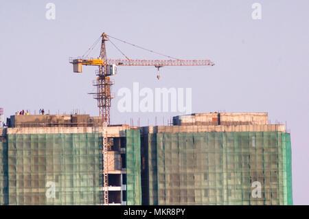 Im Bau Gebäude mit der konkreten Struktur ausgesetzt und mit grünen Sicherheitsnetze abgedeckt. Der Baukran auf der Oberseite ist eine wesentliche Voraussetzung für den Bau dieser Hochhaus Wolkenkratzer in Delhi, Jaipur, Noida, Gurgaon, Hyderabad, Bangalore, Hyderabad und andere indische Städte - Stockfoto
