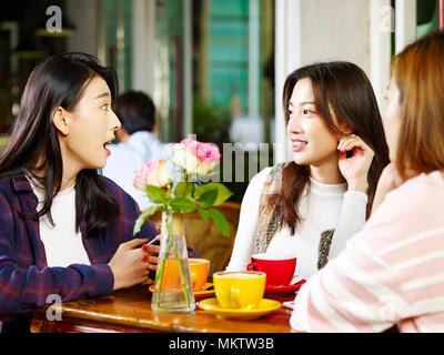 Drei glückliche wunderschöne junge asiatische Frauen am Tisch sitzen, plaudern, im Café oder Tee Haus. - Stockfoto