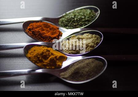 Gewürze farbige in Silber Löffel, auf einem schwarzen Holztisch gelegt. Pfeffer, Pfeffer, Salz, Basilikum, Senf - Stockfoto