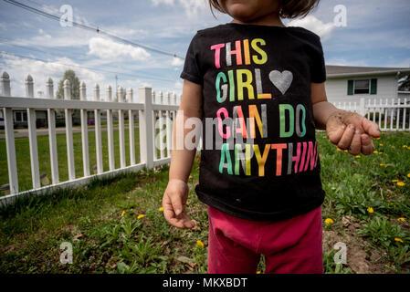 Ein kleines Mädchen, ohne ihr Gesicht zu sehen ist, trägt ein T-Shirt in einem Garten mit einem weißen Zaun hinter ihr. - Stockfoto