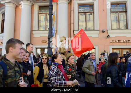 Junge in Uniform des 2. Weltkrieges auf den Schultern seines Vaters mit einer Flagge auf der Prozession am Newskij Prospekt, St. Petersburg, Russland - Stockfoto