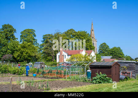 Zuteilung in einem englischen Dorf an einem sonnigen Tag mit Kirchturm im Hintergrund - Stockfoto