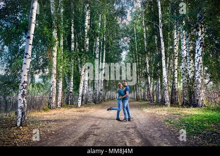 Glückliches Paar in Karo-hemden Umarmungen auf der Straße in Birke in Kirgisistan - Stockfoto