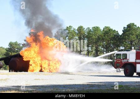 Us Air Force Feuerwehrmänner, der Bauingenieur 169th Squadron, South Carolina Air National Guard, vollständigen jährlichen Flugzeugbrand Qualifikation mit 20 Bauingenieur Squadron bei Shaw Air Force Base, South Carolina, 16. September 2017 zugewiesen. Szenarien erfordern die Feuerwehrleute die Flammen auf verschiedene Weise, einschließlich Gehen im Flugzeug Struktur mit Schutzkleidung zu nähern. Um ihre Zertifizierung auf dem Laufenden zu bleiben, die Feuerwehr muss Zug sowohl manuelle als auch auf dem Fahrzeug montierten Schläuche an der Flugzeuge Simulator, der mit einem Propan Brandbeschleuniger in Brand gesetzt wird. (U.S. Ai - Stockfoto