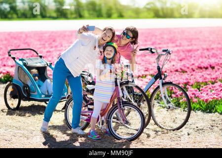 Holländische Familie Reiten Fahrrad in der Tulpe Blume Felder in den Niederlanden. Mutter und Kinder unter selfie Bild mit Handy Kamera auf Fahrräder bei blühenden - Stockfoto
