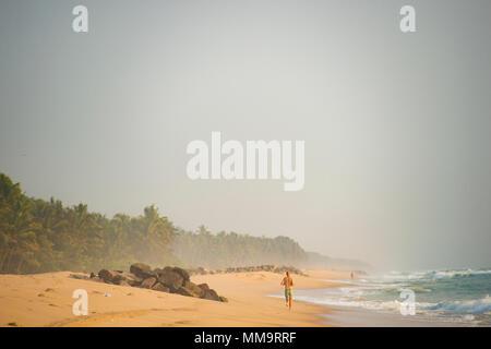 Ein Mann in einem Badeanzug läuft am Strand bei Sonnenuntergang. Varkala tropischen Strand, Kerala, Indien. - Stockfoto