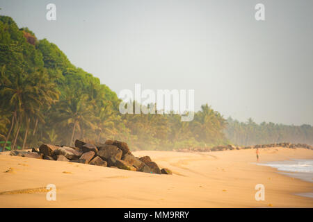 'Selektiven focus' ein Mann in einem Badeanzug am Strand bei Sonnenuntergang ausgeführt wird. Varkala tropischen Strand, Kerala, Indien. - Stockfoto