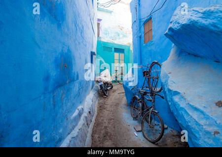 Ein Fahrrad- und ein Motorrad in einer kleinen Gasse in die blaue Stadt Jodhpur, Rajasthan, Indien. - Stockfoto