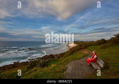 Eine Frau auf den eigenen saß auf einer Bank am Boambee landspitze am Murray Beach, New South Wales, NSW, Australien suchen - Stockfoto