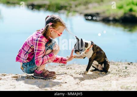 Kind, Mädchen spielen mit Boston Terrier Hund auf dem sandigen Ufer im Freien - Stockfoto
