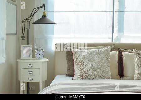 Luxuriöse Schlafzimmer mit Lampe und Wecker auf hölzernen Tisch zu Hause - Stockfoto