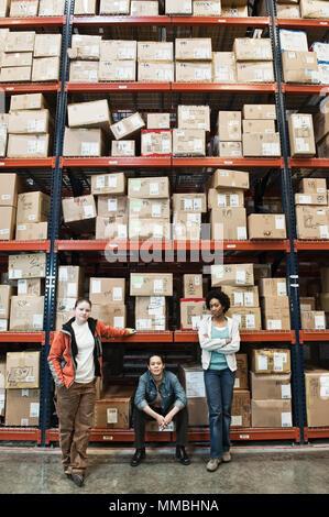 Team Portrait der multi-ethnischen weiblichen Lagerarbeiter in einer großen distrubiton Lager voll von Produkten auf Paletten in Kartons gelagert auf großen - Stockfoto