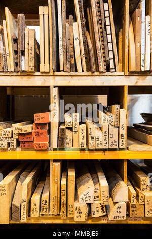 Große Auswahl an Brettern und Boards auf Regalen in einem Lager gestapelt. - Stockfoto