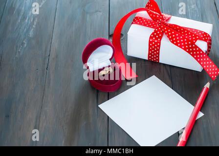 Geschenk mit roter Schleife, Herz, mit einem Ring am Valentinstag - Stockfoto