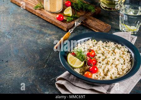Licht diätetische Lebensmittel, Couscous mit Tomaten, Kalk und frischen Kräutern in dunklen Schüssel, dunkelblauen Hintergrund Kopie Raum - Stockfoto