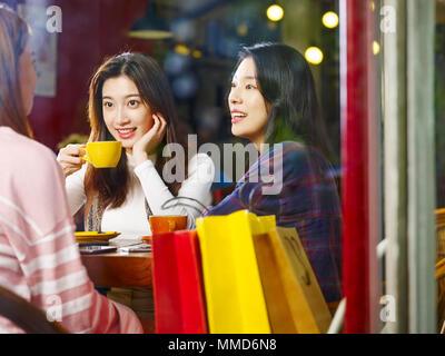 Drei glückliche wunderschöne junge asiatische Frauen am Tisch sitzen, plaudern, im Café oder Tee Haus nach dem Einkaufen, Schuß durch Fensterglas. - Stockfoto