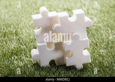 Ansicht von vier weißen Puzzle auf grünem Gras - Stockfoto