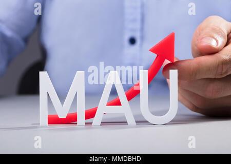 Geschäftsmann berühren Rot Erhöhung der monatlichen Aktive Benutzer Pfeil auf Schreibtisch - Stockfoto
