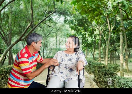 Ältere Paare im Park, Frau sitzend auf Rollstuhl, und Ehemann sprechen - Stockfoto