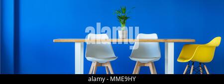 ... Anlage Auf Einem Großen Holztisch Und Moderne Kunststoff Weiße Und  Gelbe Stühle In Einem Blauen Speisesaal