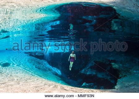 Ein Mädchen Flächen in das klare Wasser, die sich aus dem Kalkstein Feder am blauen Feder vent. - Stockfoto
