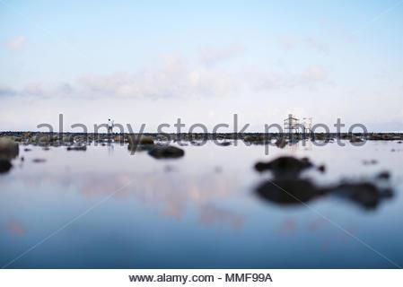 Ein Mann geht über die gesamte freiliegende Riff zu der Brandung zerschlagen. - Stockfoto