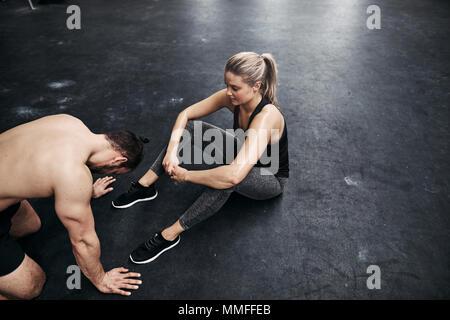 Junge passen Mann, auf dem Boden einer Turnhalle nach dem Training Session mit seinem trainingspartner erschöpft - Stockfoto