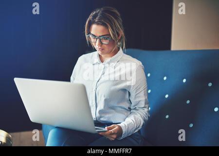 Junge Geschäftsfrau Brillen online arbeiten mit einem Laptop auf dem Sofa zu Hause sitzen - Stockfoto