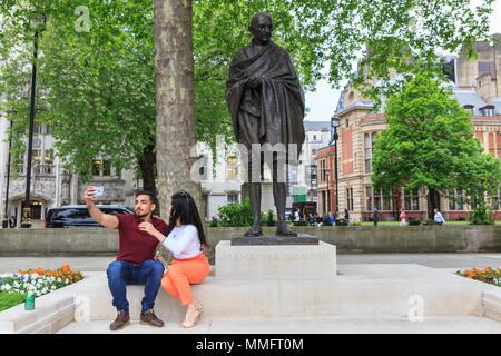 Westminster, London, 11. Mai 2018. Ein paar nehmen selfies vor dem Mahatma Gandhi Statue in Parliament Square. Trotz der bewölkt und etwas kältere Wetter, Touristen um Westminster und South Bank sind in großen Zahlen genießen Sie die Sehenswürdigkeiten der britischen Hauptstadt. Credit: Imageplotter Nachrichten und Sport/Alamy leben Nachrichten - Stockfoto