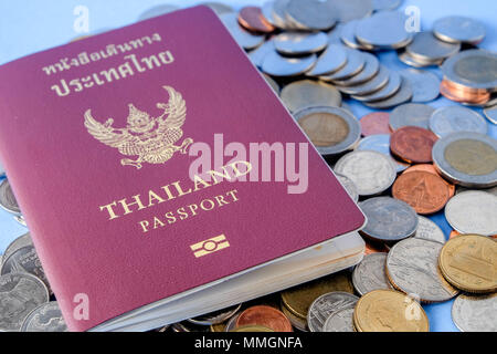 Thailand Reisepass braun umfassen und Geld Münze auf blauem Papier Hintergrund für Reisen - Stockfoto