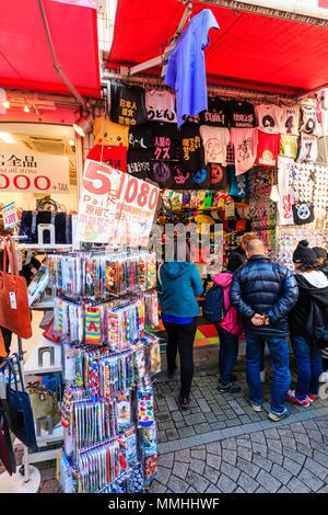 Tokio, Harajuku, Takeshita Straße. T-Shirt und Socken Shop, Außen, verschiedene Kleidung draussen auf Display, Menschen im Eingang stehen. - Stockfoto