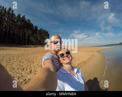 Wandern am Ufer des Meeres. Hübsche junge Liebende Paar selfie zusammen auf dem Smartphone am Strand. - Stockfoto