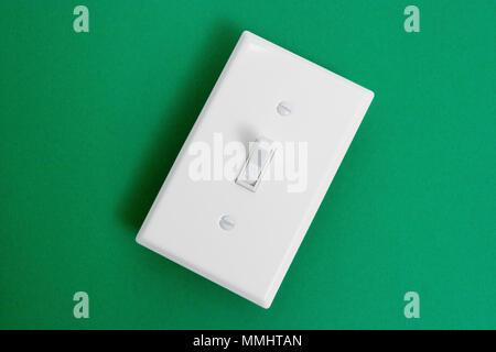 Umweltfreundliche, erneuerbare Energie, Weiß elektrischer Schalter auf grünem Hintergrund - Stockfoto