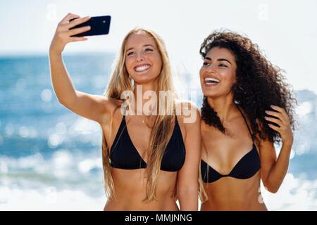 Zwei junge Frauen, die selfie Foto mit smart phone in Badekleidung an einem tropischen Strand. Lustig, kaukasischen und arabischen Frauen in schwarzen Bikini. - Stockfoto