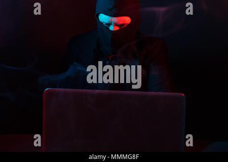 Wütend Computerhacker in Anzug stehlen Daten vom Laptop durch rote und blaue Licht beleuchtet - Stockfoto
