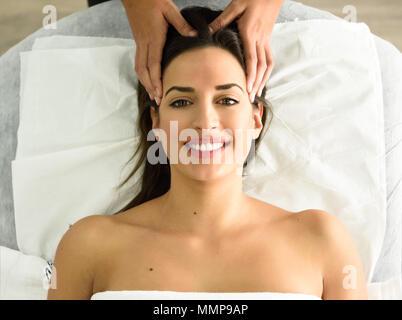 Blick von oben auf die jungen kaukasischen lächelnde Frau mit einem Kopf Massage im Spa. Weibliche Patienten ist, die Behandlung von professionellen Therapeuten. - Stockfoto