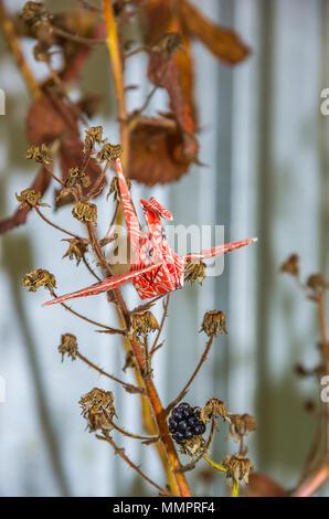 Origami Papier Kran aus original japanischen Origami Papier in einem natürlichen Garten Umgebung eingerichtet. - Stockfoto