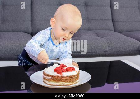 Der erste Geburtstag Feier eines kleinen Jungen. Little Boy essen Geburtstag Kuchen mit einem Löffel, alles Gute zum Geburtstag. Kleinkind am Tisch mit Kuchen. - Stockfoto