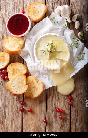 Geschmolzene würzige Camembert mit Knoblauch, Thymian und Olivenöl close-up auf den Tisch. Vertikal oben Ansicht von oben - Stockfoto