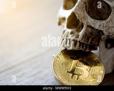 Nahaufnahme von Schädel beißen Golden bitcoin auf hölzernen Tisch. Das Konzept der Investition und die Fluktuation der bitcoin und cryptocurrency. Das Gefühl der enttäuschend - Stockfoto