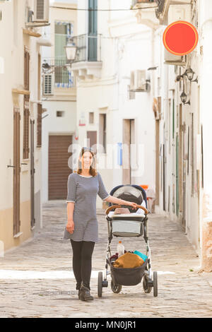 Gallipoli, Apulien, Italien - eine Frau mit ihrem Baby in den Straßen von Gallipoli - Stockfoto