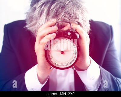 Man versteckt sich hinter Wecker auf weißem Hintergrund. Zeit-management Konzept - Stockfoto