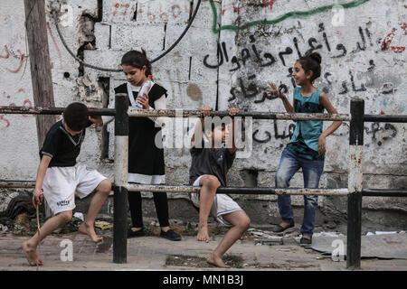 Gaza, Palästina. 13. Mai, 2018. Palästinensischen Flüchtlinge Kinder draußen spielen die Häuser ihrer Familien an der palästinensischen Flüchtlingslager Jabalia in Jabalia, nördlichen Gazastreifen, 13. Mai 2018. Rund fünf Millionen palästinensischen Flüchtlinge Gedenken der 68. Jahrestag der Nakba Tag (Tag der Katastrophe) am 15. Mai, die die Vertreibung vor und der Israelischen Unabhängigkeitserklärung 1948 gefolgt. Foto: Wissam Nassar/dpa