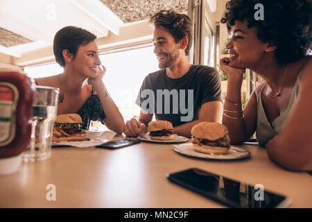 Eine Gruppe von Freunden in einem Restaurant mit einem gestapelten Burger auf dem Tisch sitzen. Glückliche junge Mann mit seinen weiblichen Freunden zusammen im Cafe und hav Sitzen - Stockfoto