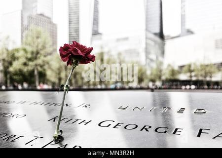 Blumen links in Gedenken an die Opfer des 11. September 2001 Angriff; das Denkmal 9/11 Pools, Downtown New York, New York City USA (siehe auch MN3R 26. - Stockfoto