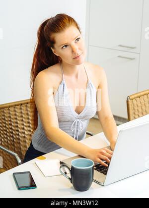 Foto von einer schönen jungen Frau mit roten Haaren sitzt mit Laptop und Kaffee zu trinken. - Stockfoto