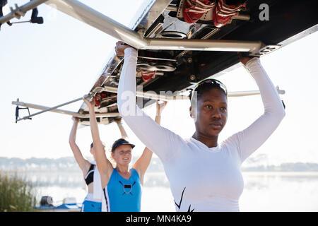 Zuversichtlich , weiblich rudernde Mannschaft anheben scull Overhead - Stockfoto