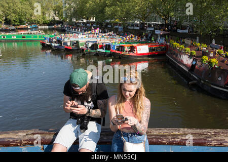 Eine tätowierte Paar in texting am Ufer des Grand Union Canal in Little Venice, London, UK - Stockfoto