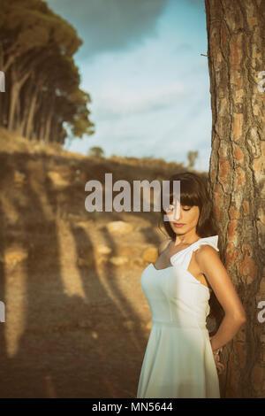 Schöne Frau, die an einen Baum gelehnt - Stockfoto